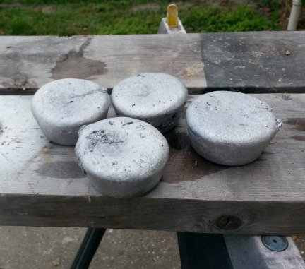 Four newly cast ingots of aluminum.